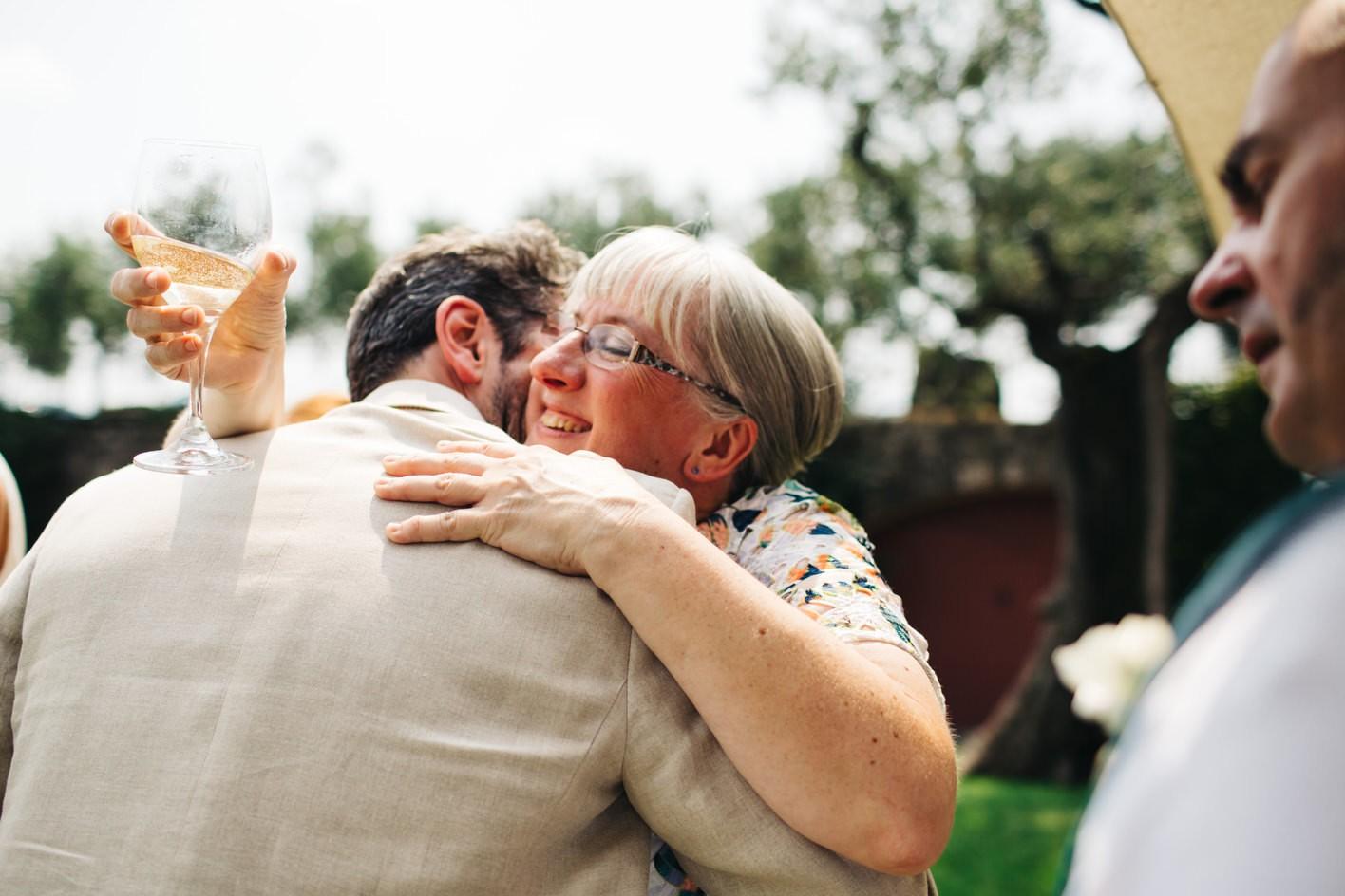 Mother of the bride hugs groom