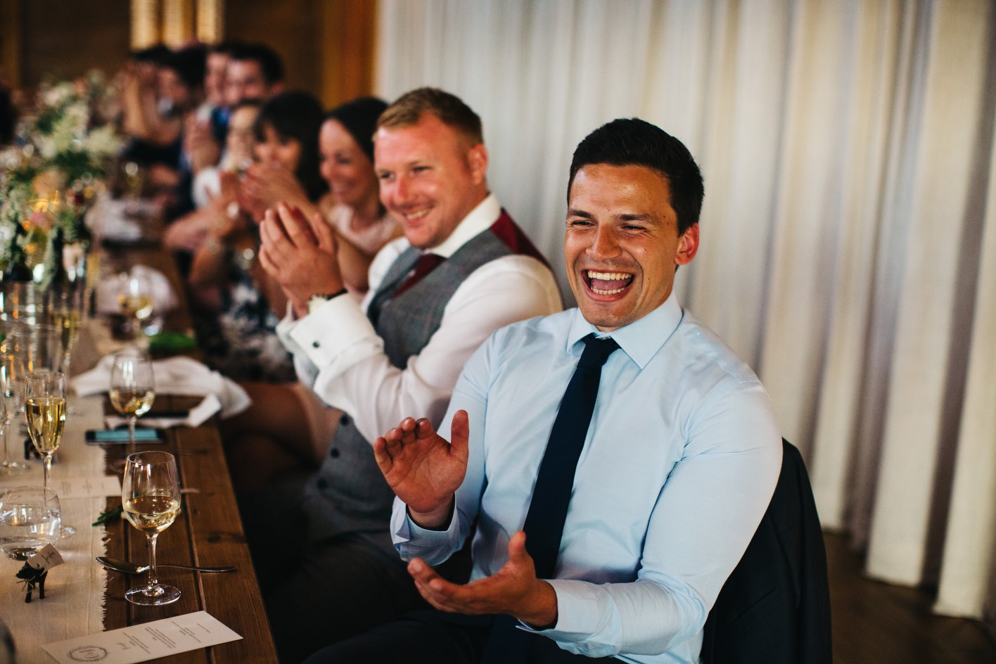 guests laugh during speeches at cotswolds wedding