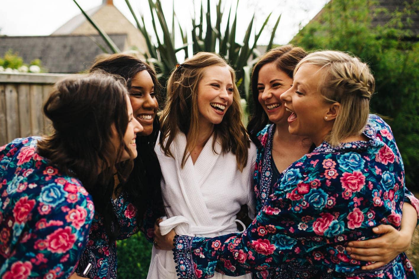 brides and bridesmaids hug before wedding