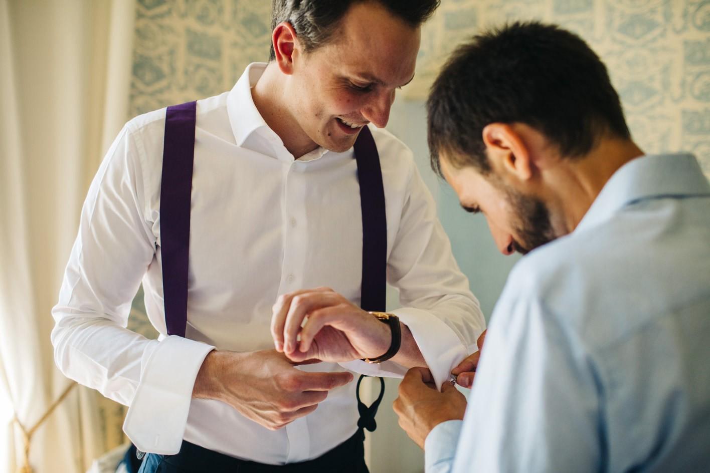 usher helps groom get ready