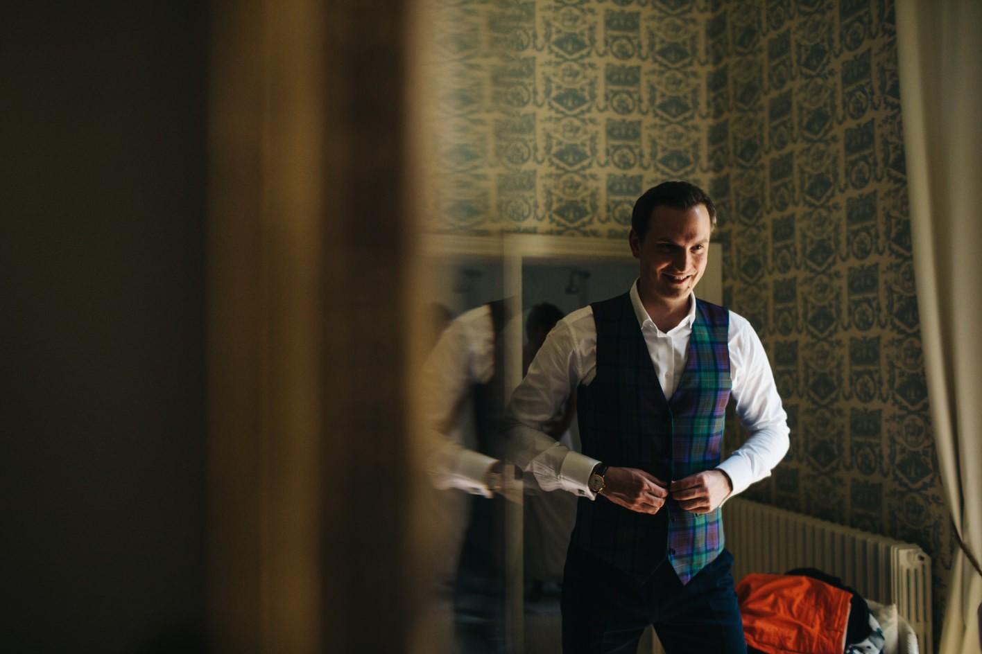 groom puts on tartan waitcoat