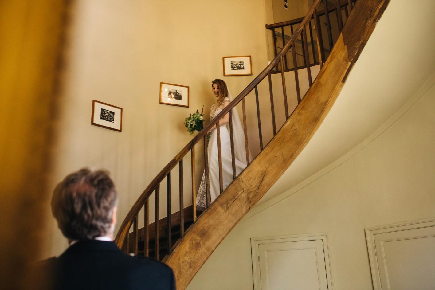 bride walks down stairs at chateau de lartigolle