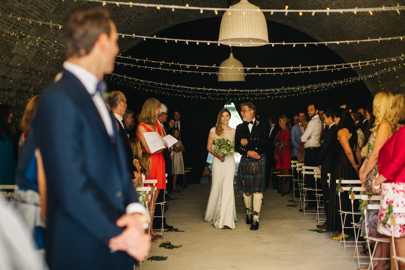 bride walks down aisle in french cellar ceremony