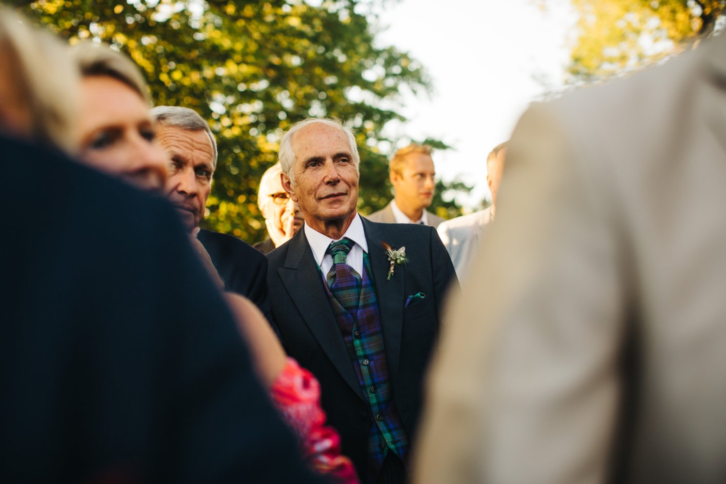 father of the groom looks at couple