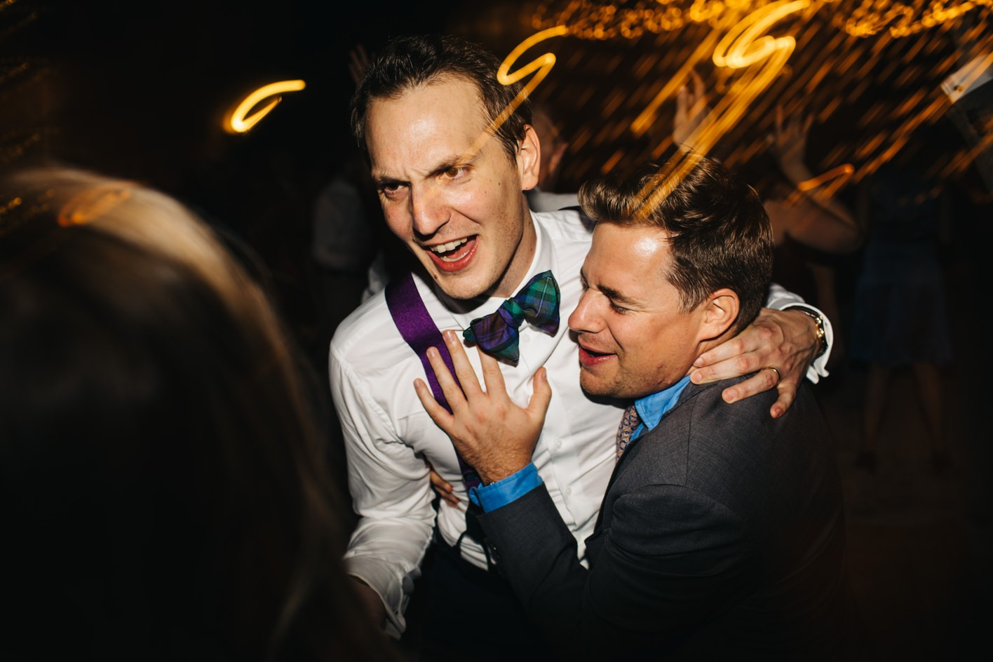 guests hugs groom on dance floor
