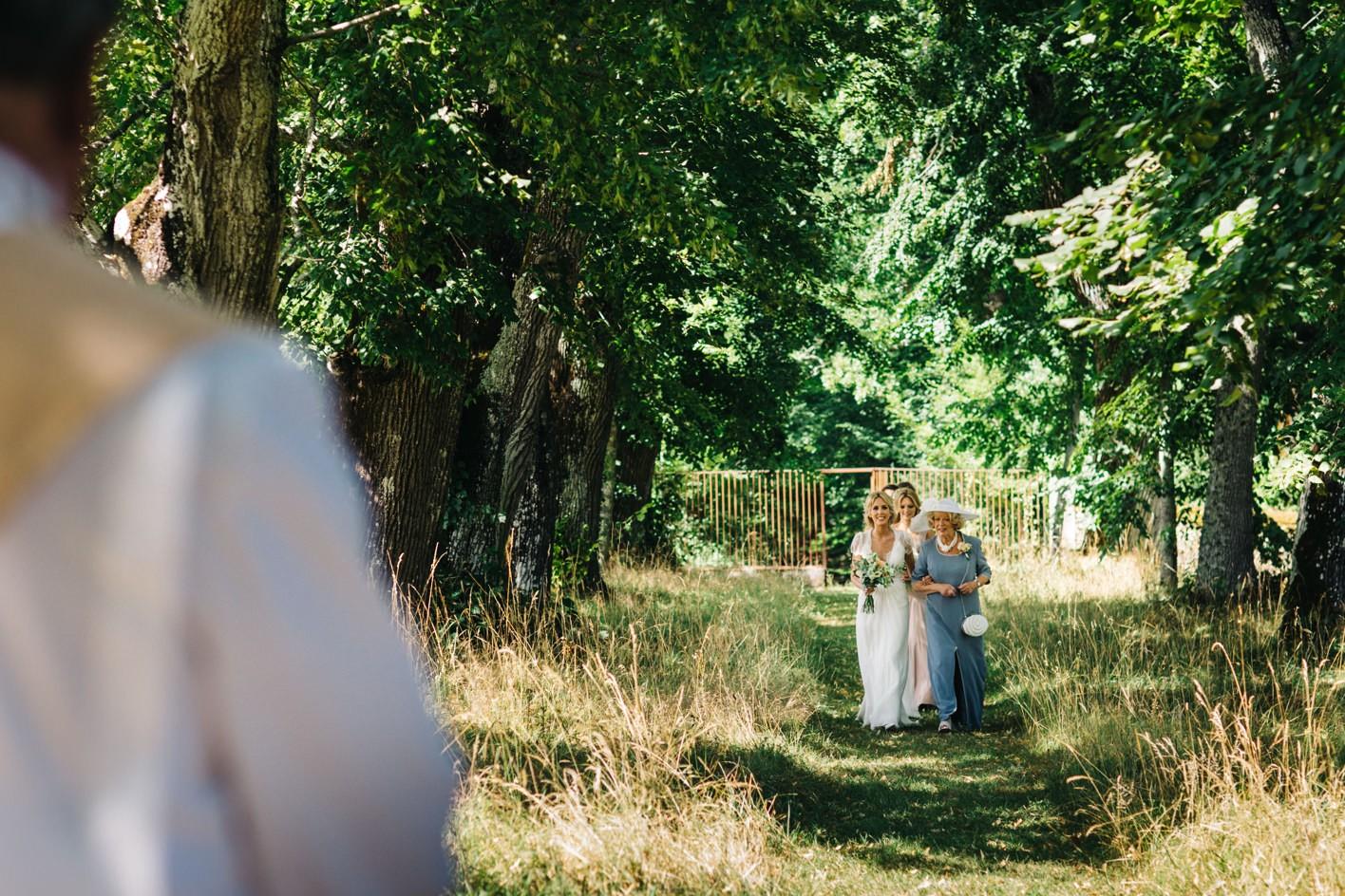 bride walks down tree wedding aisle