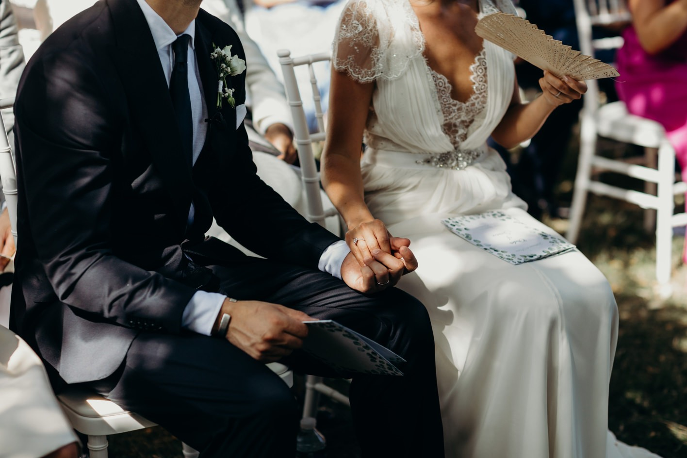 husband and wife hold hands during ceremony