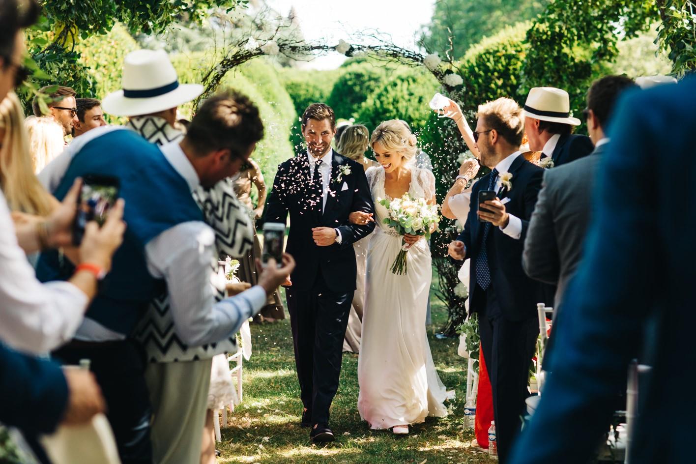 bride and groom walk down outside wedding aisle