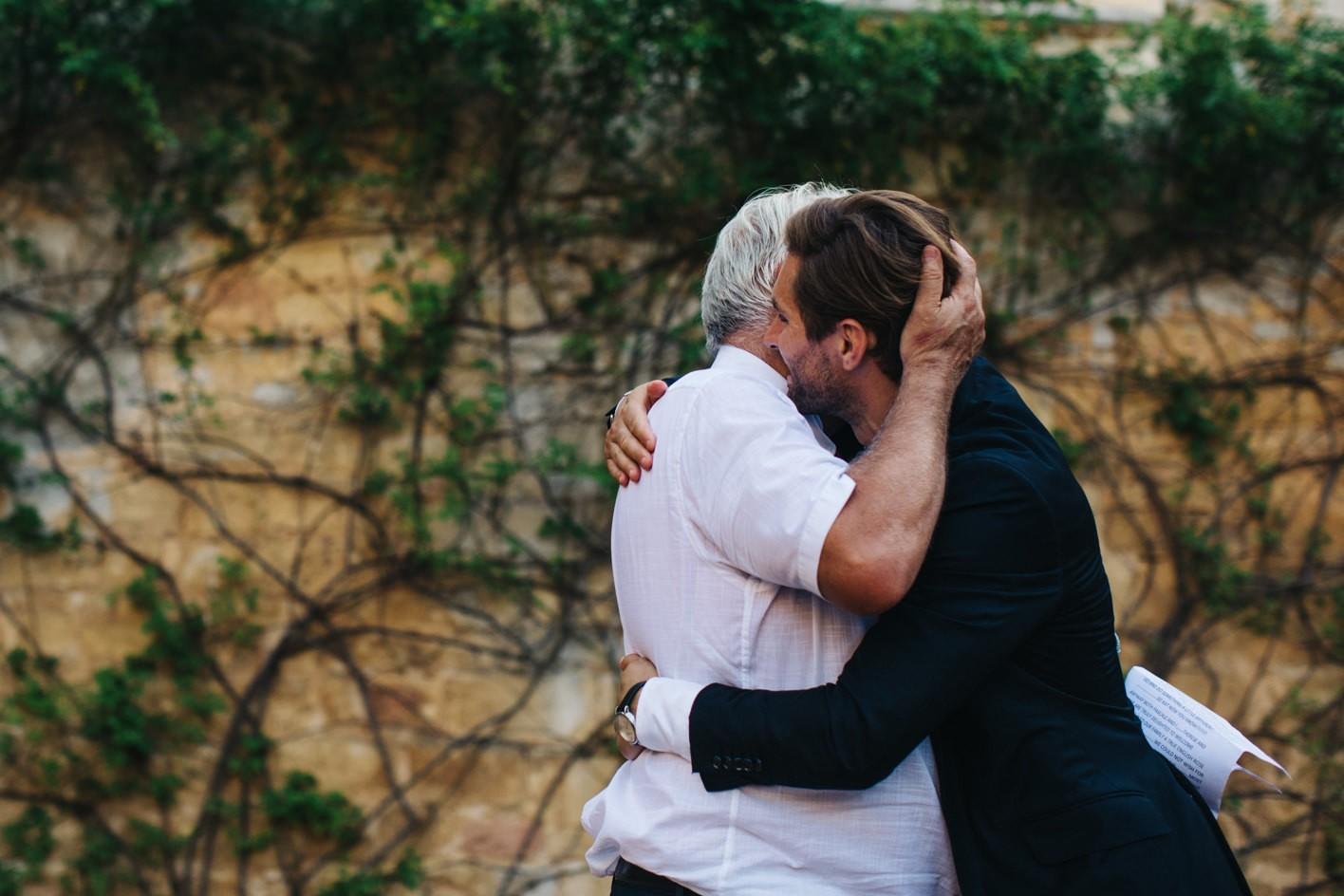 groom hugs his dad during speech