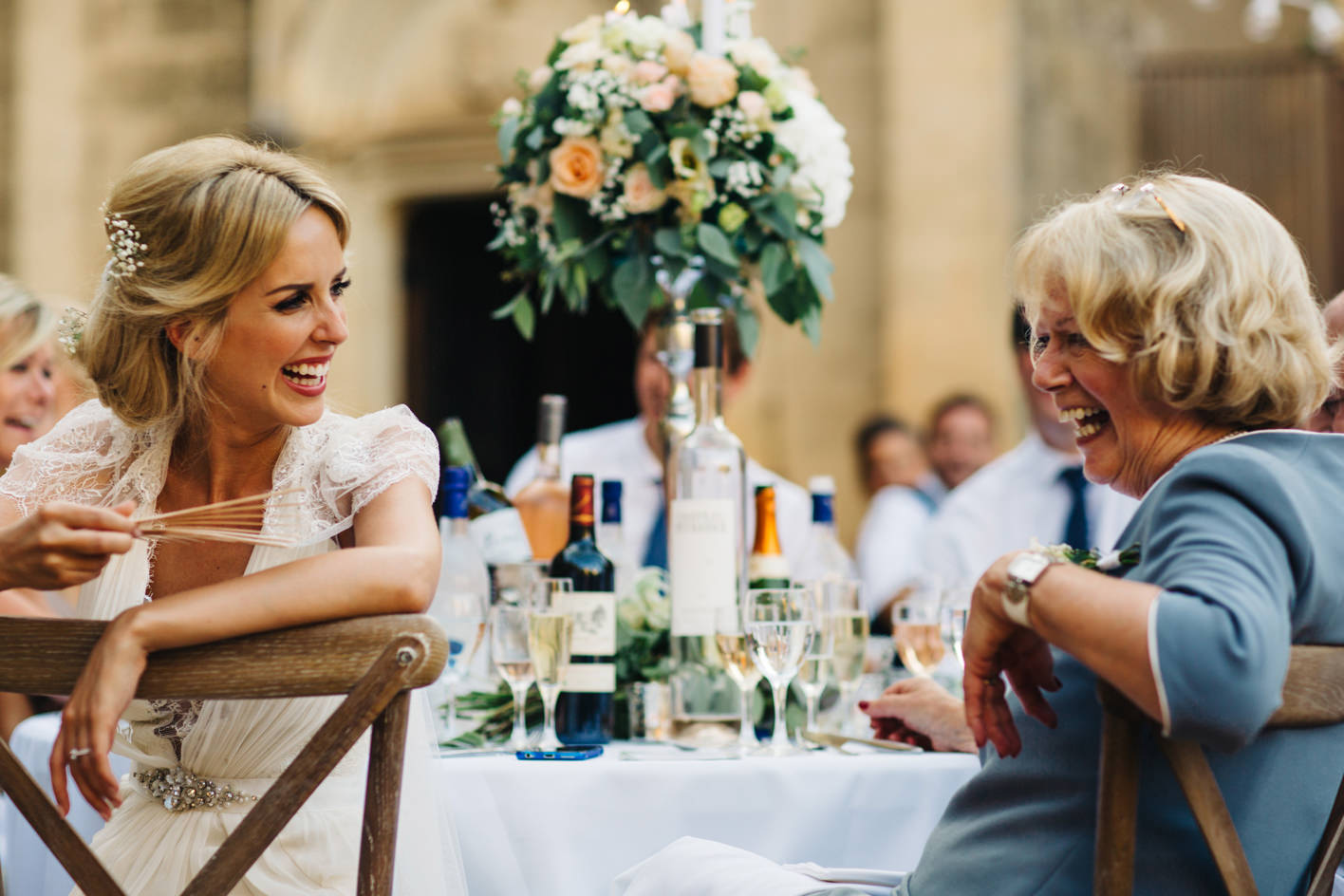 bride and mother laugh during wedding reception