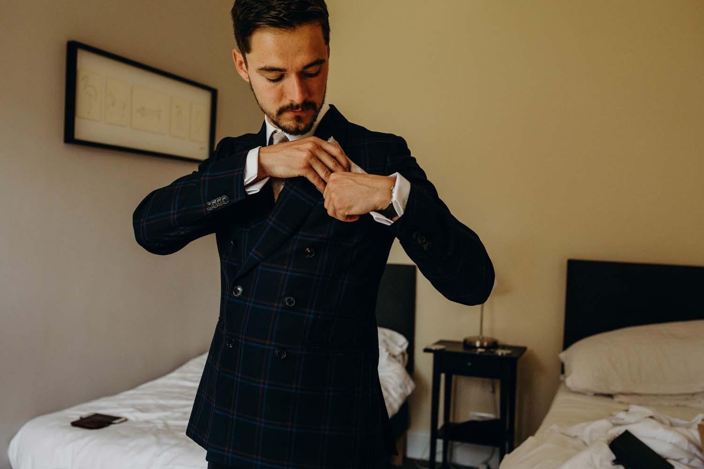 groom putting handkerchief in pocket