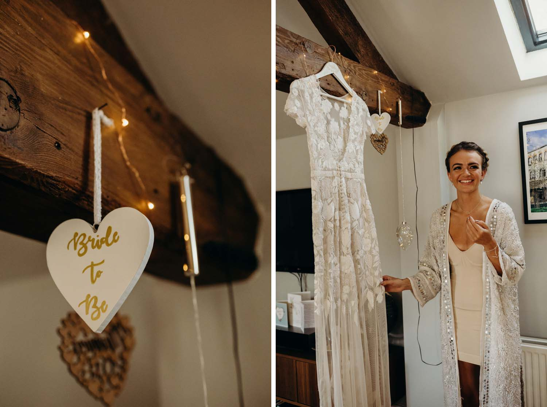 Bride smiling next to wedding dress