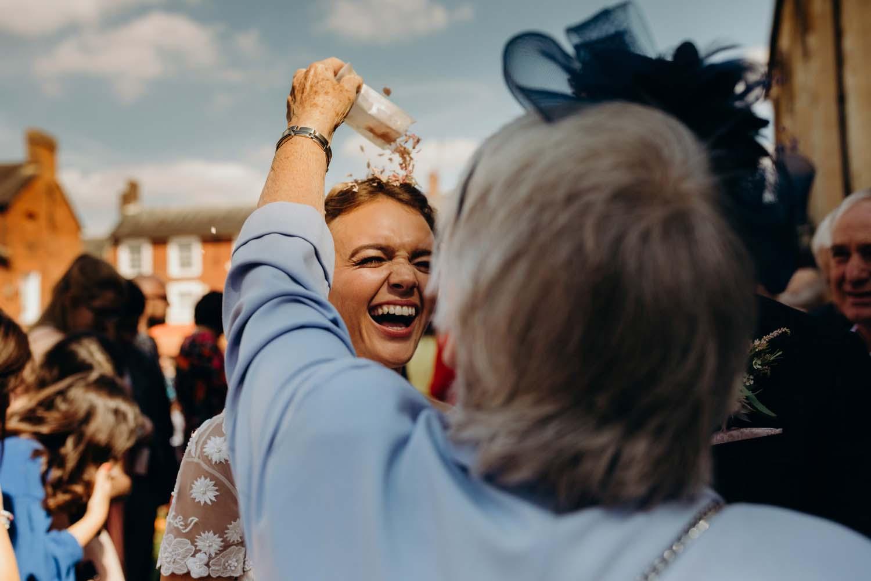 Lady pours confetti over bride