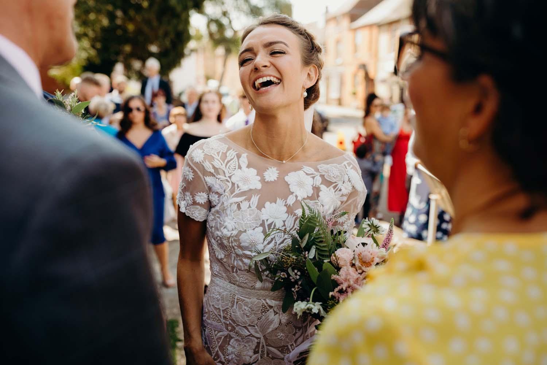 Bride laughing wearing Hermione De Paula