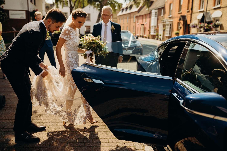 Bride walks into wedding car