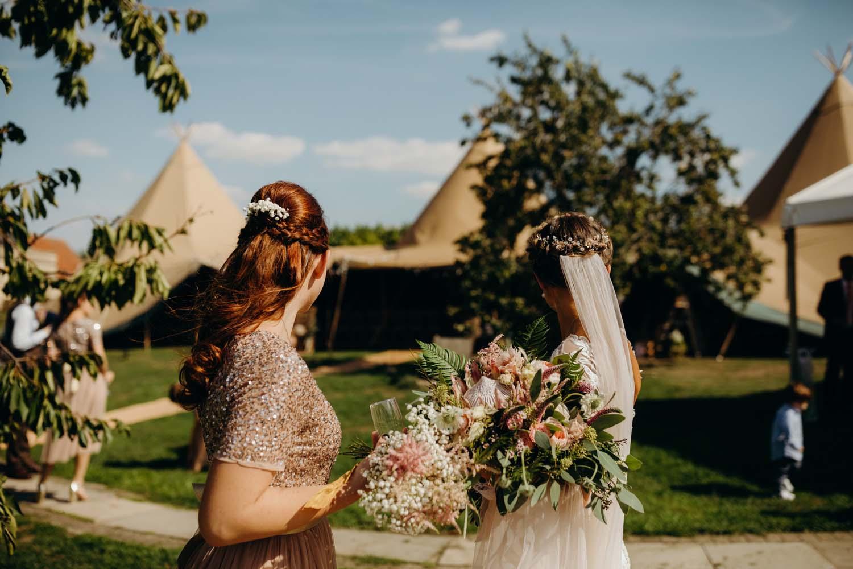 Bride looks at tipi at wedding