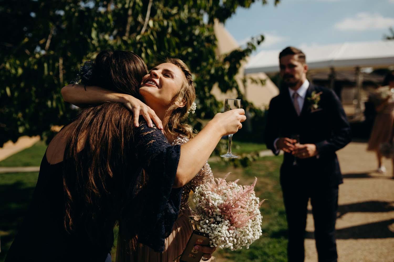Bridesmaid hugs guest