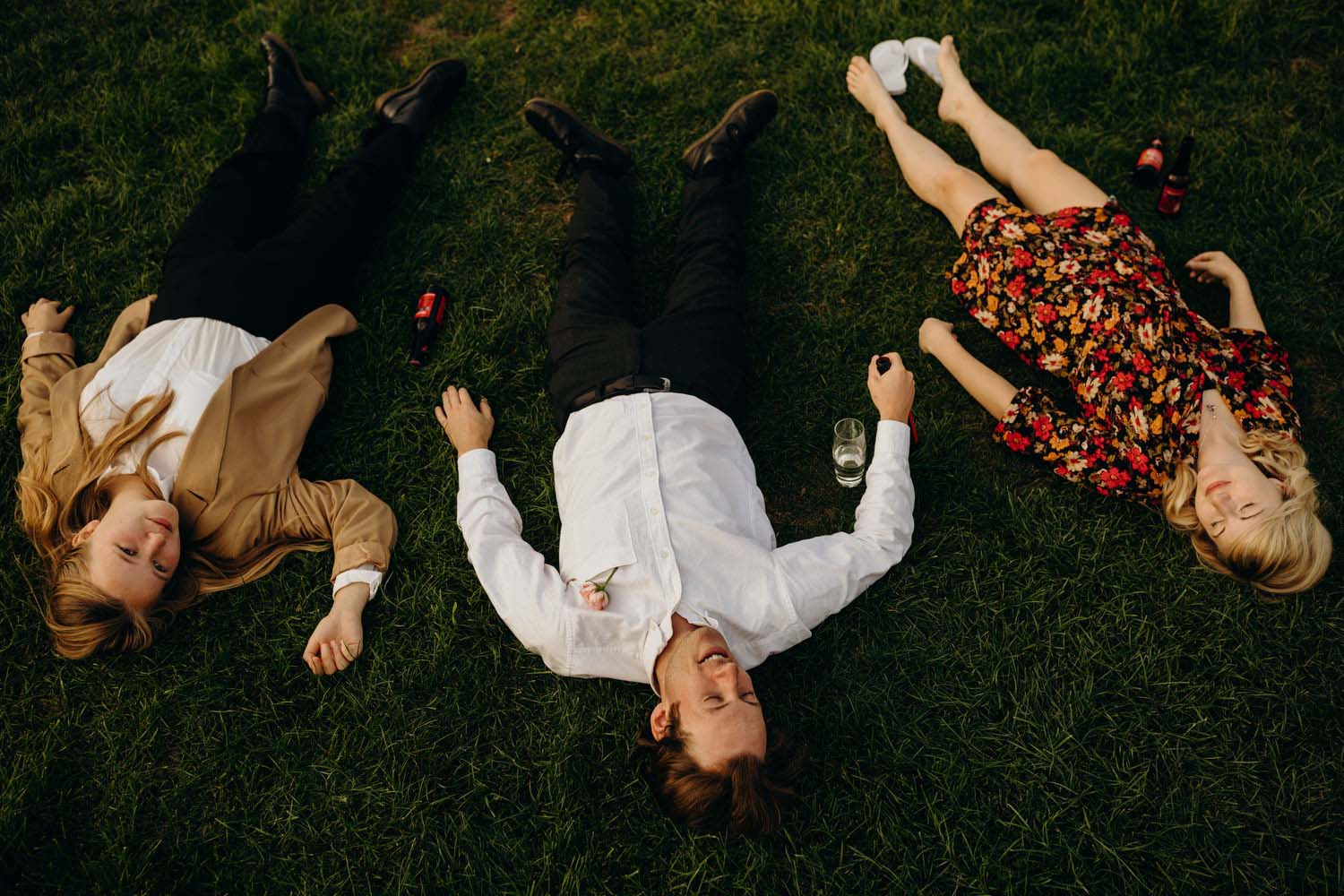 3 people lie down on grass