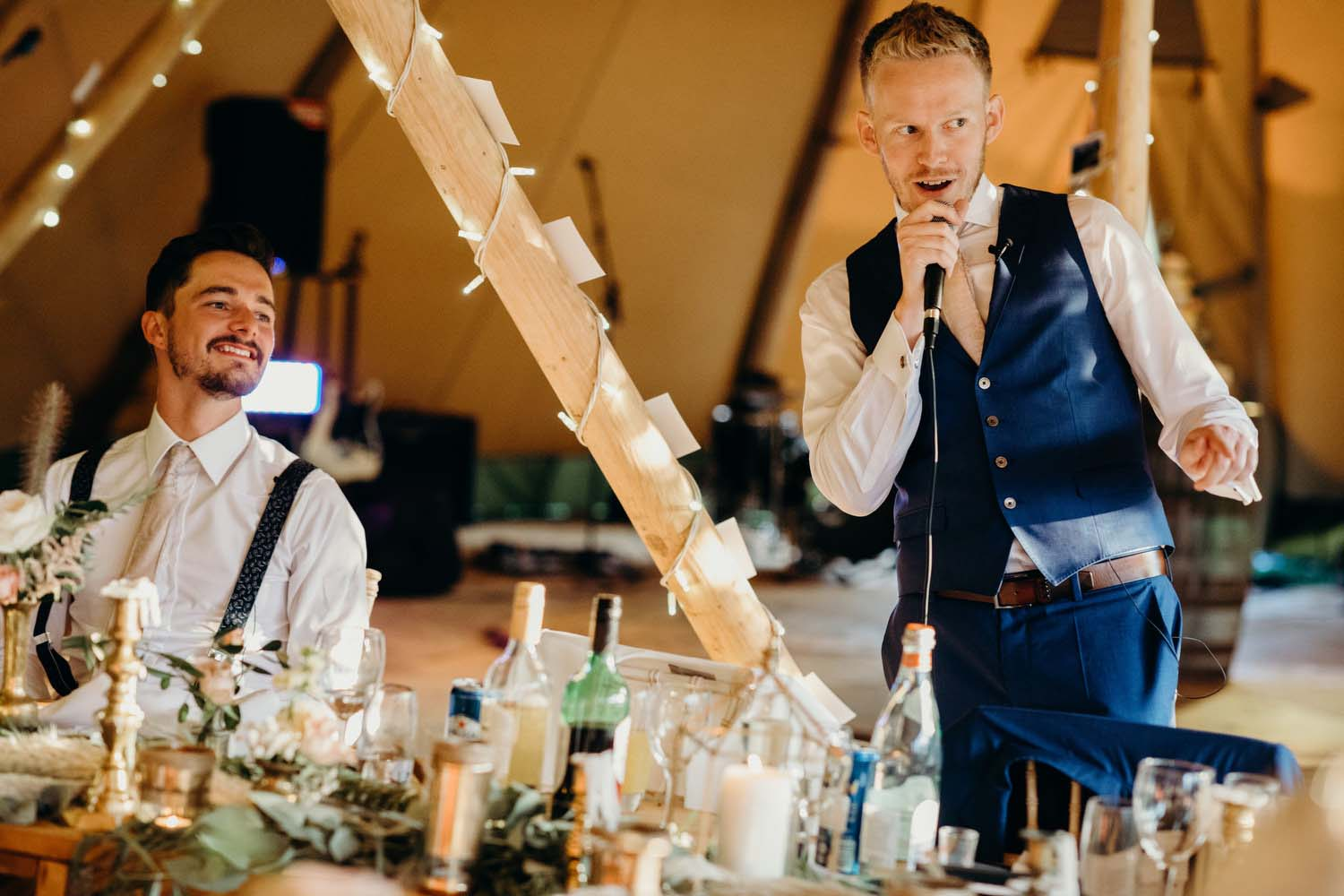 Best man does speech with groom in background