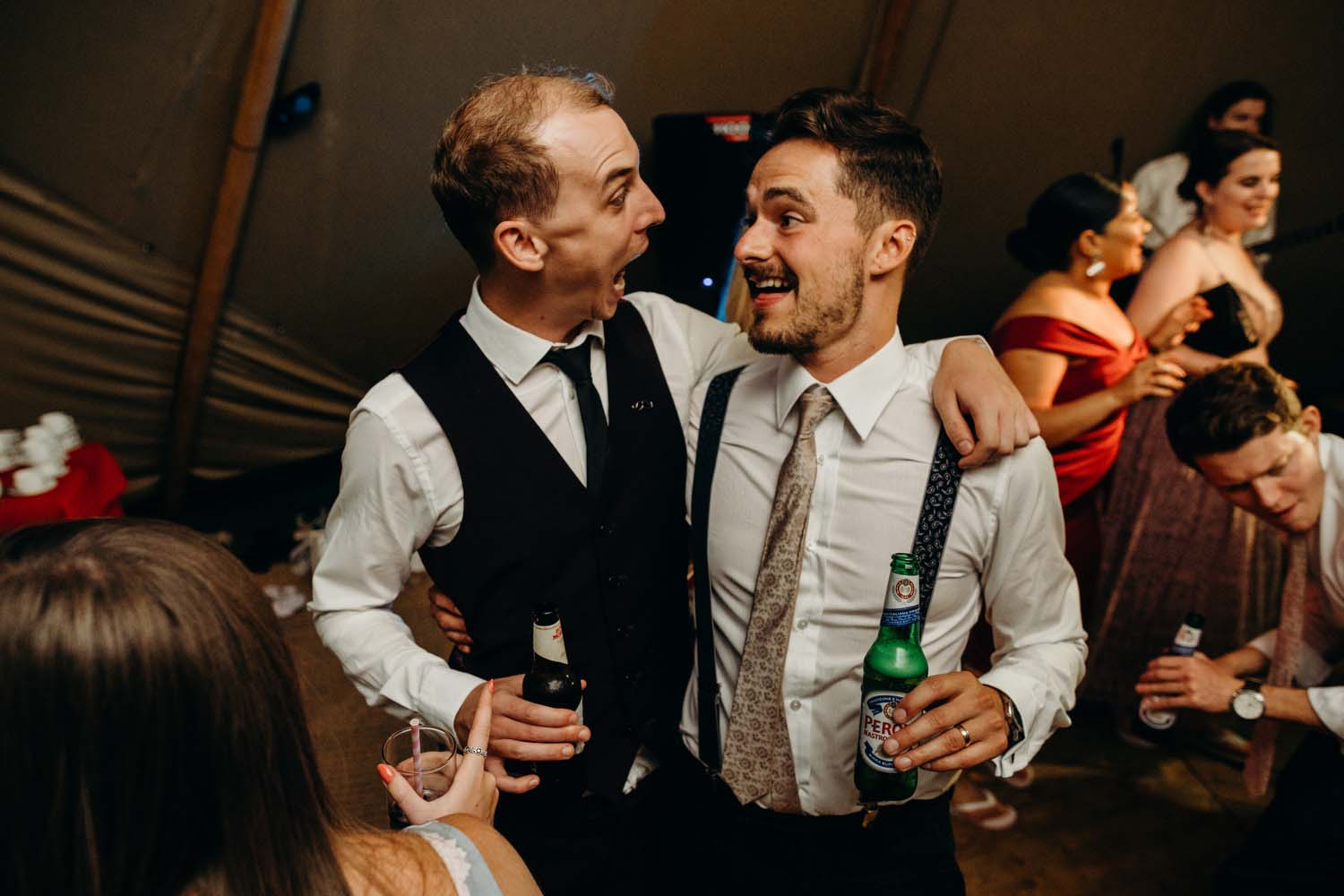 groom and friend hugging at wedding