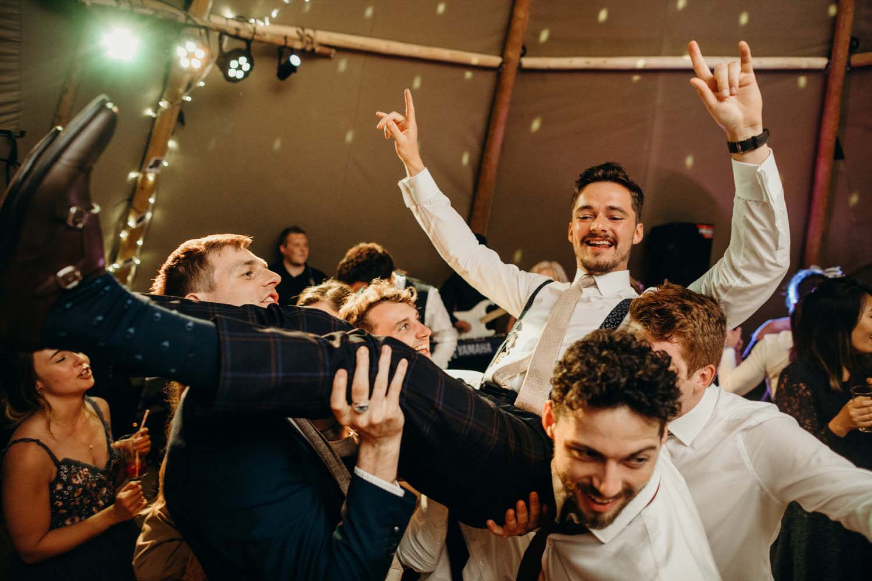 groom being picked up in air at wedding
