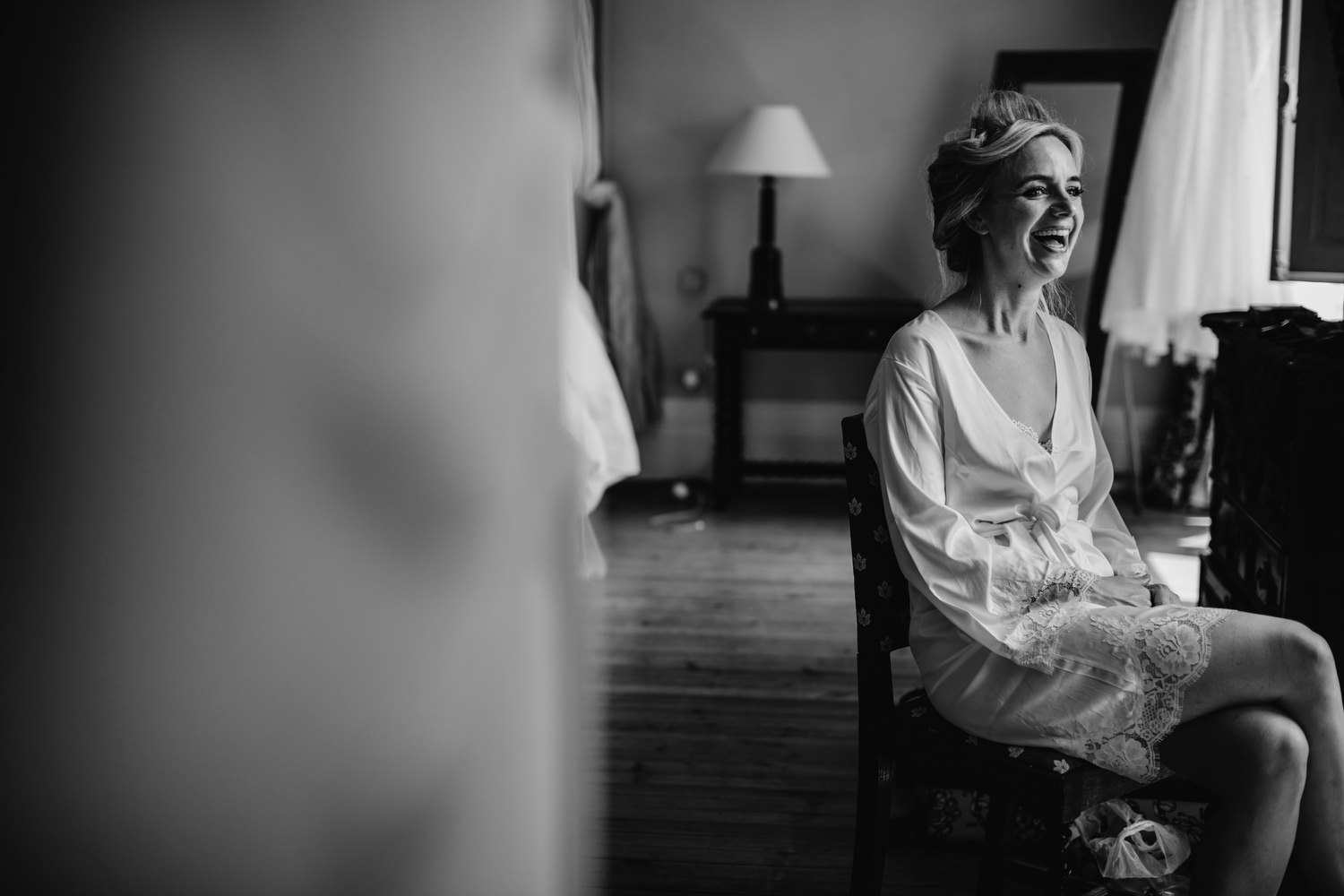 Bride laughing while having make up appied