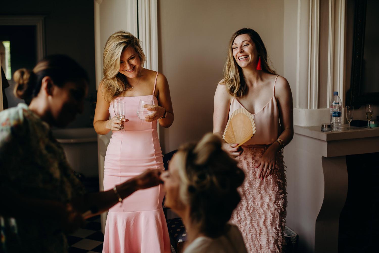 friends laugh as bride gets ready