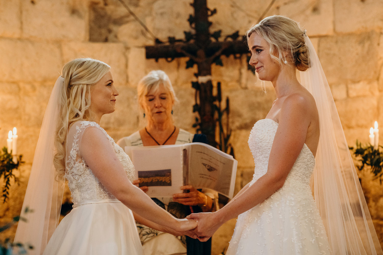 bride and bride hold hand during vows