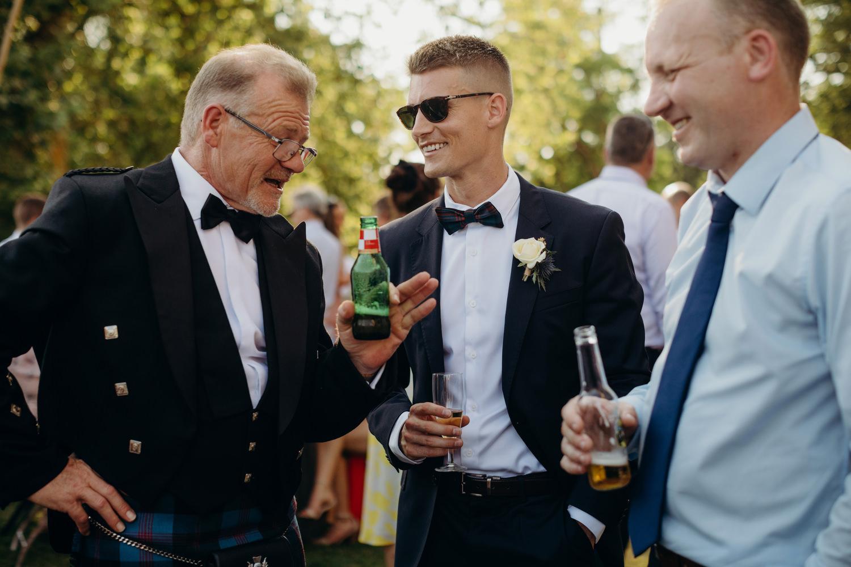 3 guys laugh at wedding