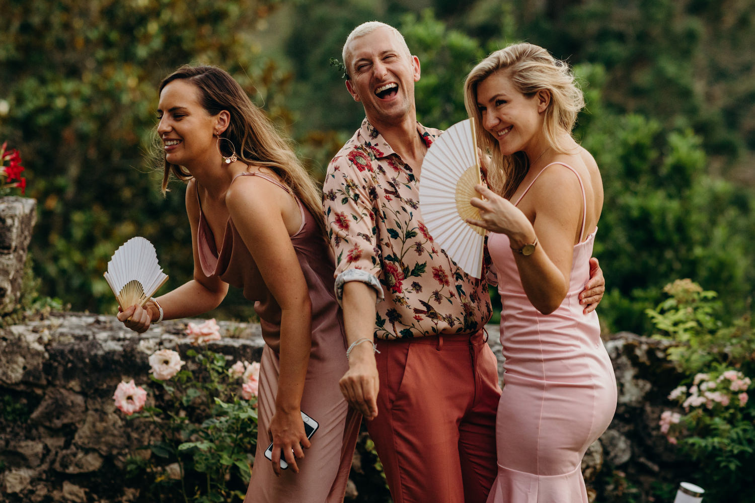 guests cooling down with fans at hot wedding
