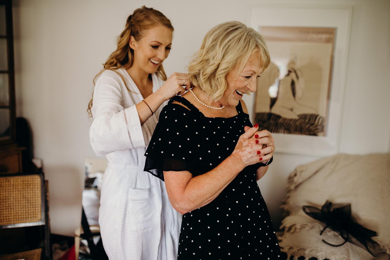 bride helping mum with jewellery