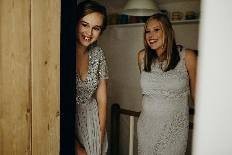 2 bridesmaids smiling looking at bride