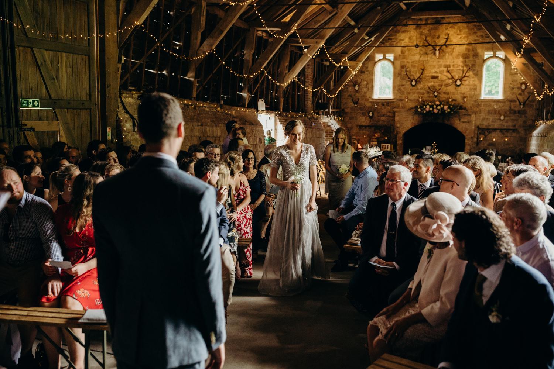bridesmaids walking down barn aisle