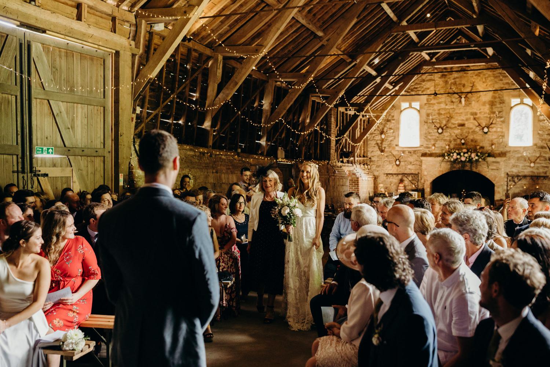 bride makes entrance to barn wedding