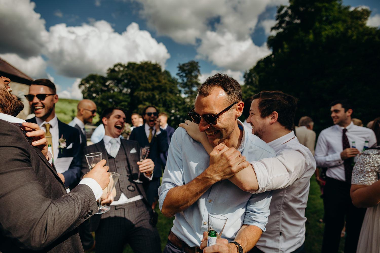 laughing guys embrace at wedding