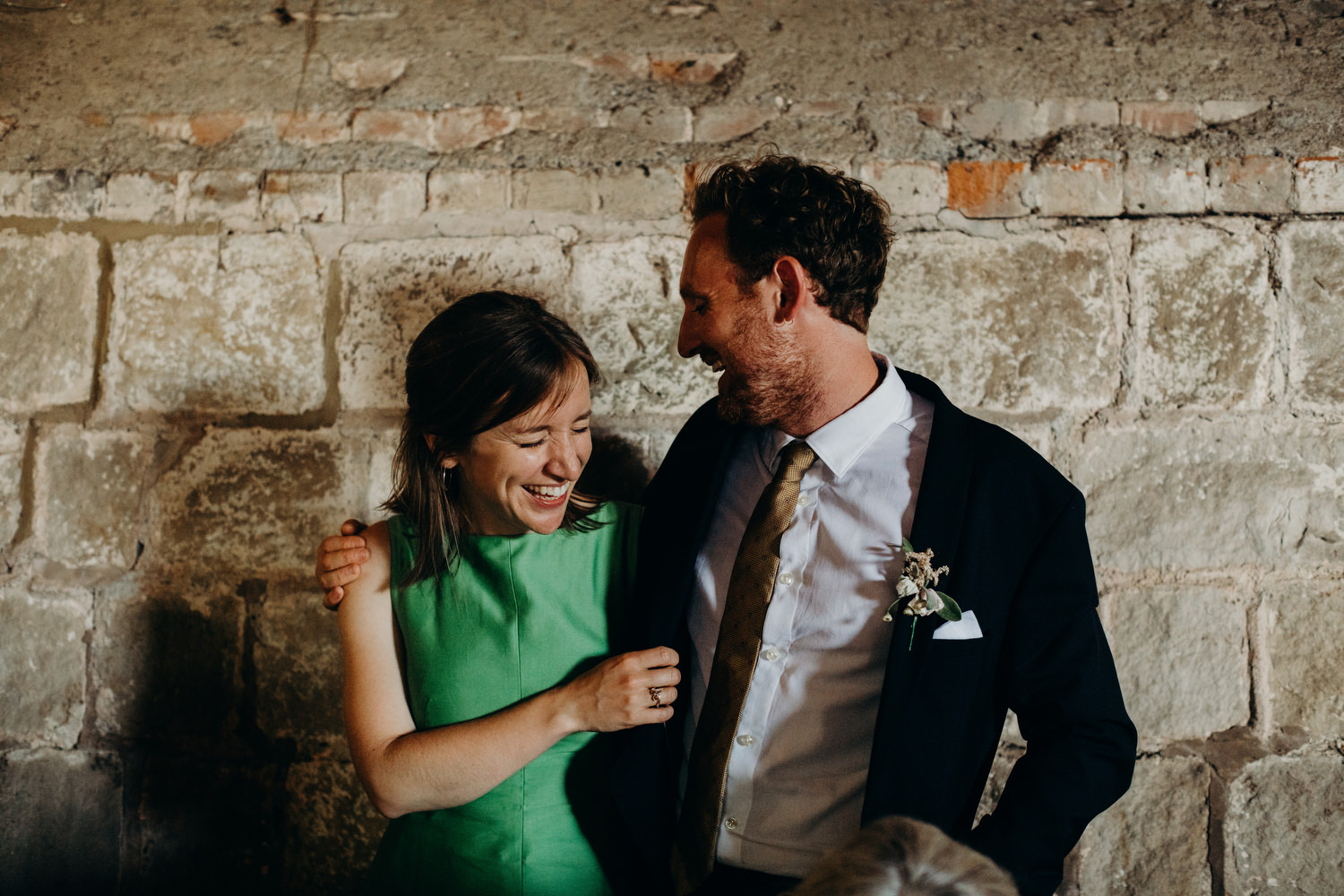 two guests laugh while embracing