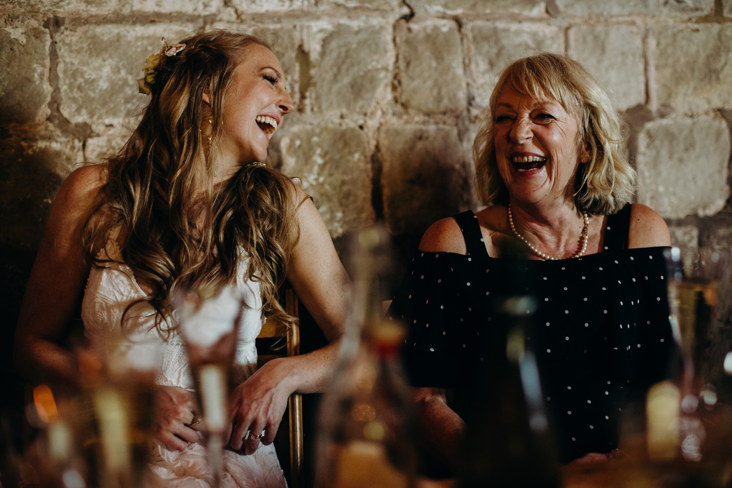 bride and mother laughing during wedding speech