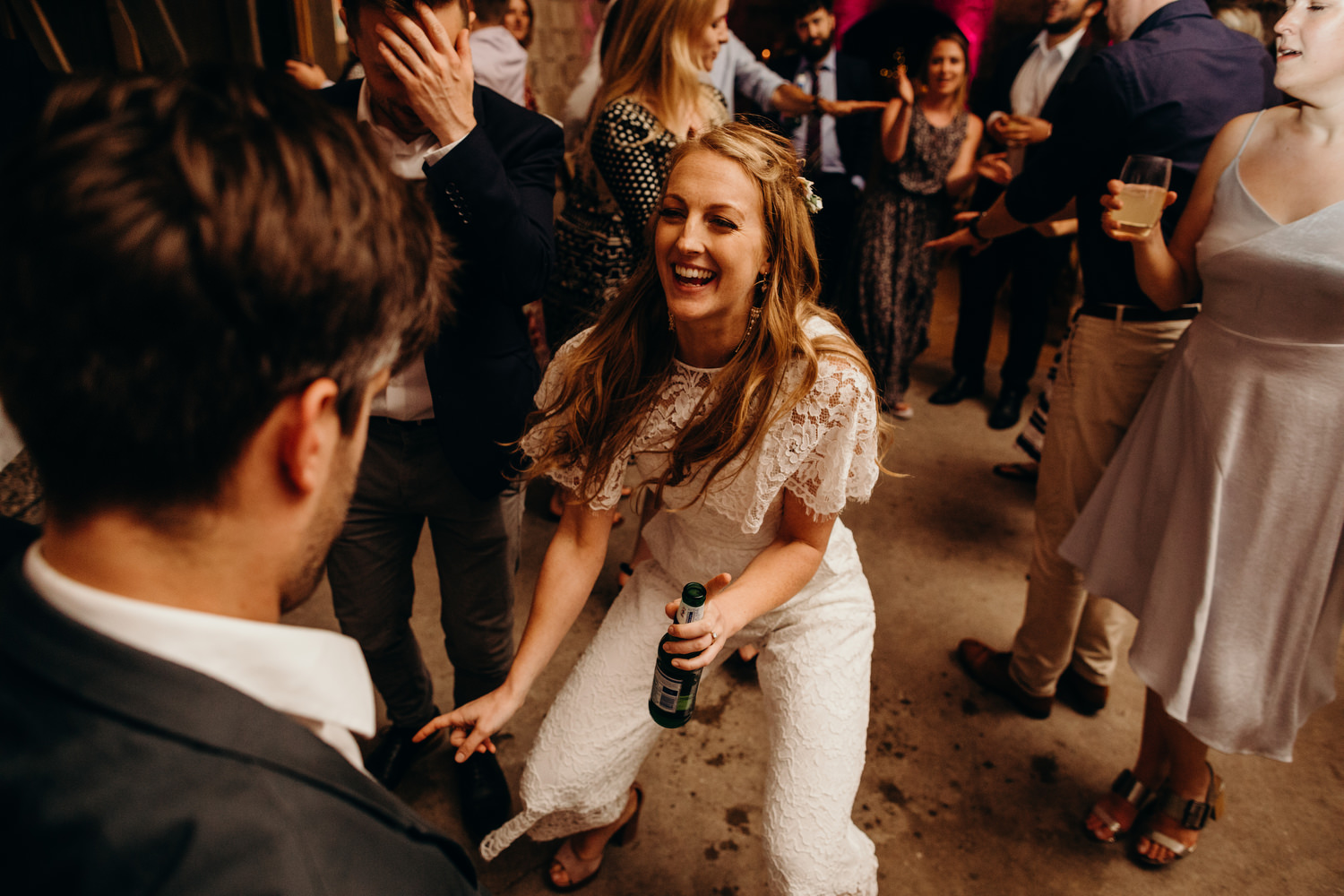 bride in a white jumpsuit at wedding