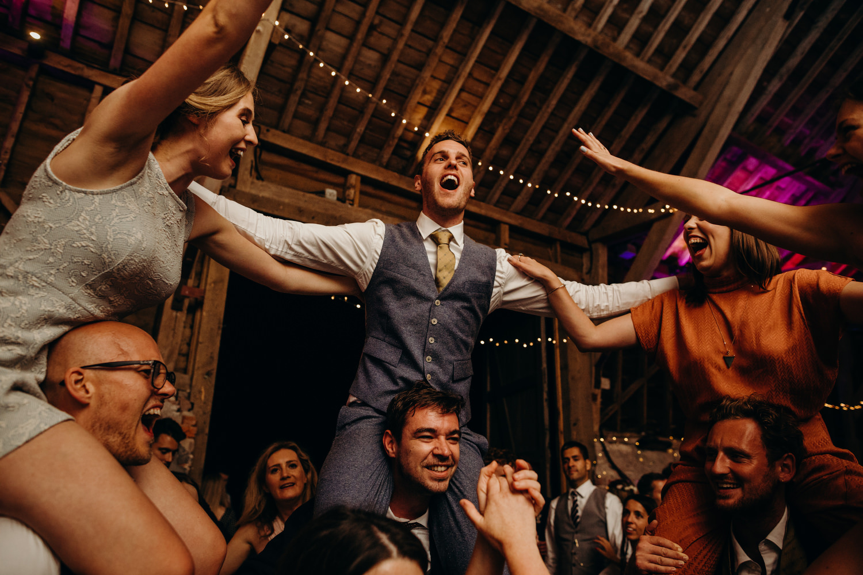 groom on shoulders of guest at wedding