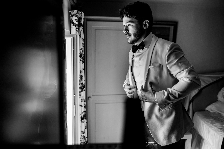 groom puts jacket on at wedding
