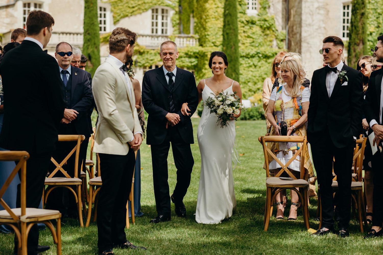 bride walks down aisle outdoor wedding