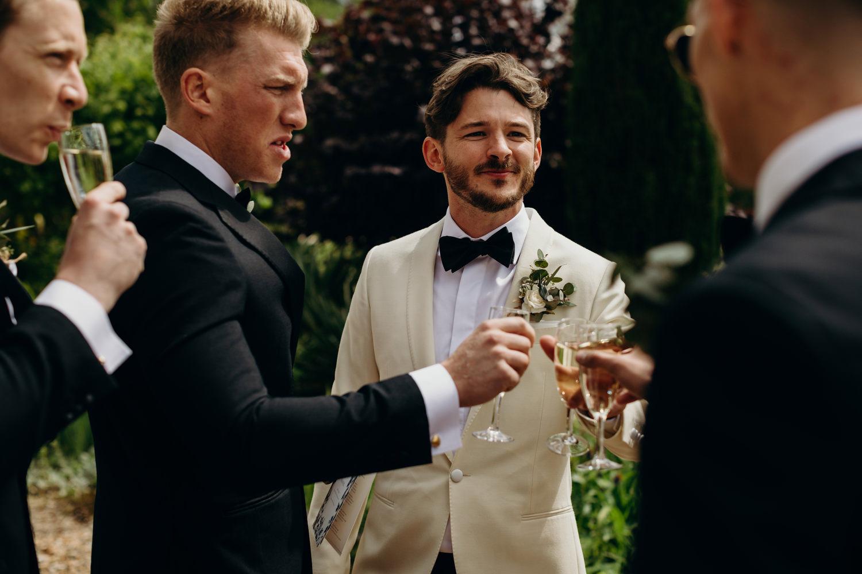 groom cheers with ushers