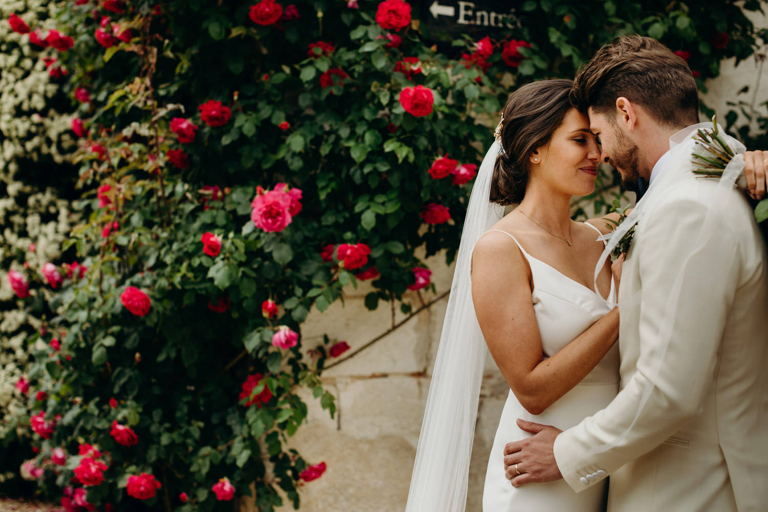 bride and groom pose with roses in background