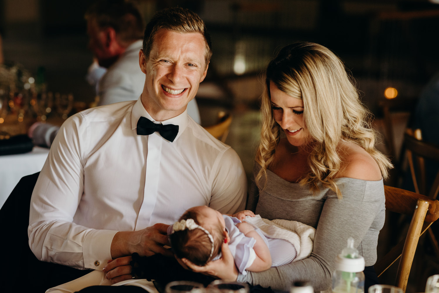 guests hold baby at wedding