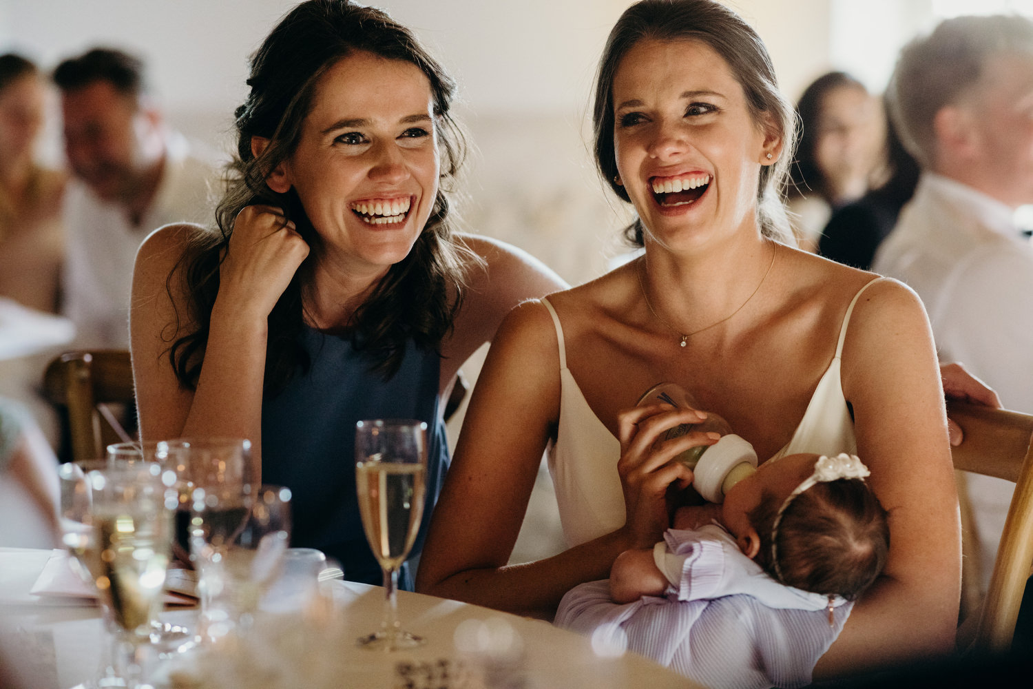 bride and sister laughing during wedding speech