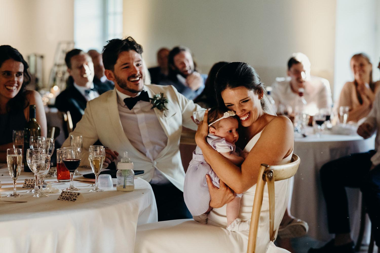 Bride hugs baby during speeches