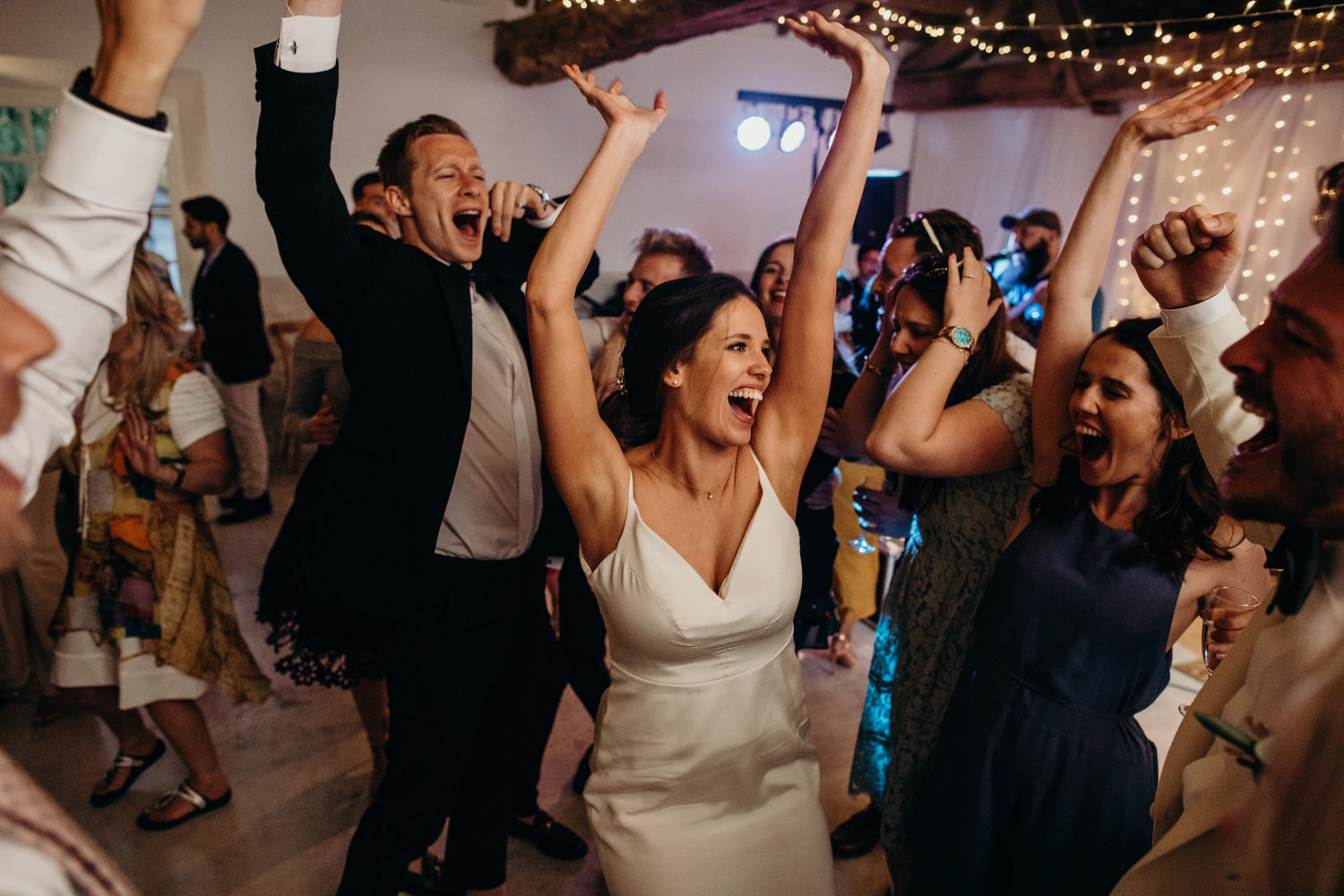 bride throws hands in air at party