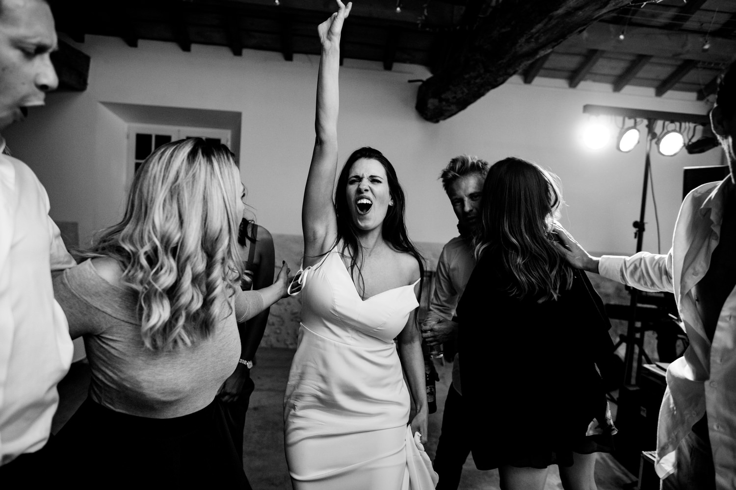 bride throws hand in air whilst dancing