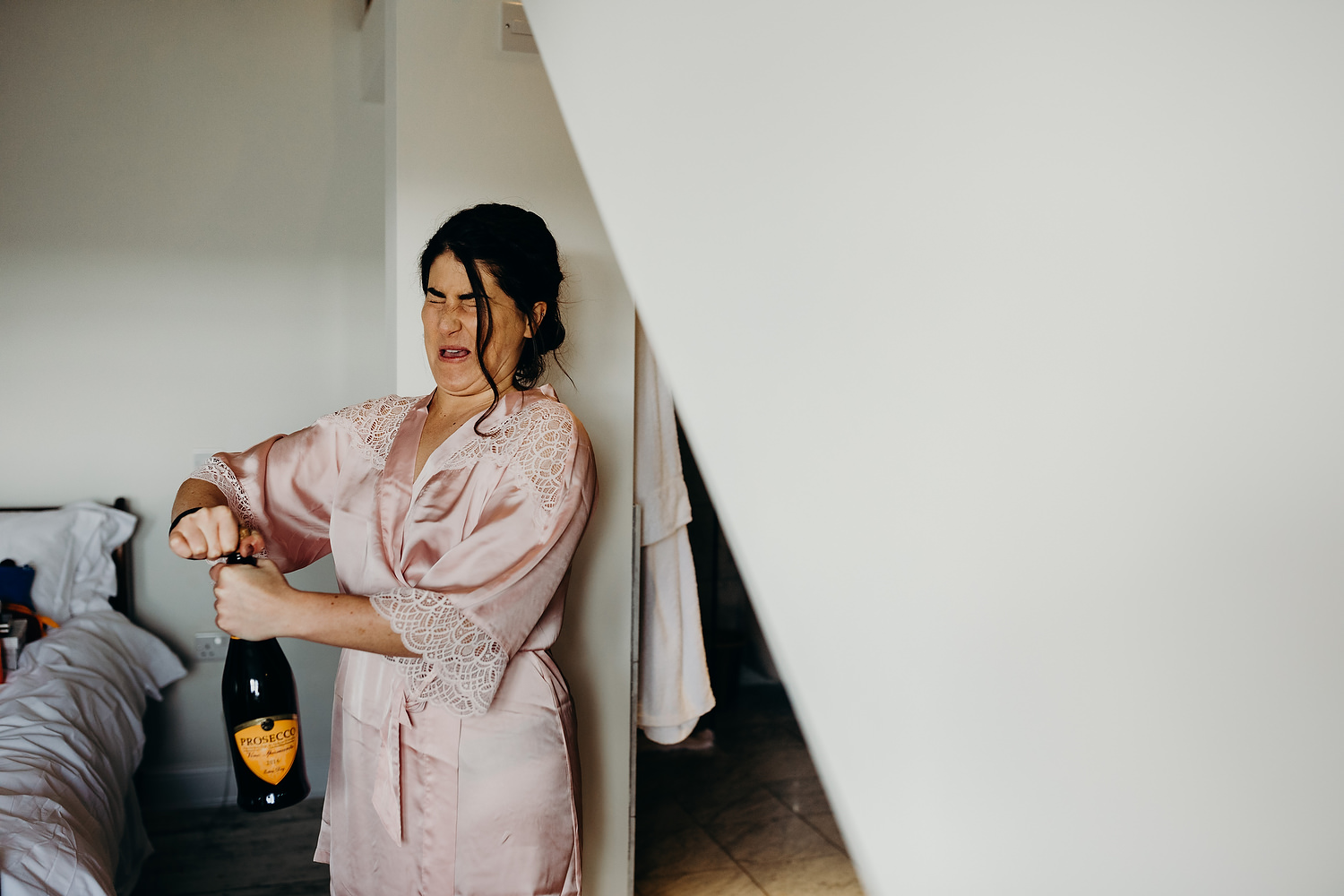 bridesmaid opens champagne