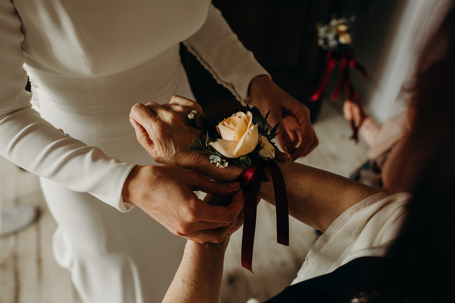 bride puts Corsage on mother